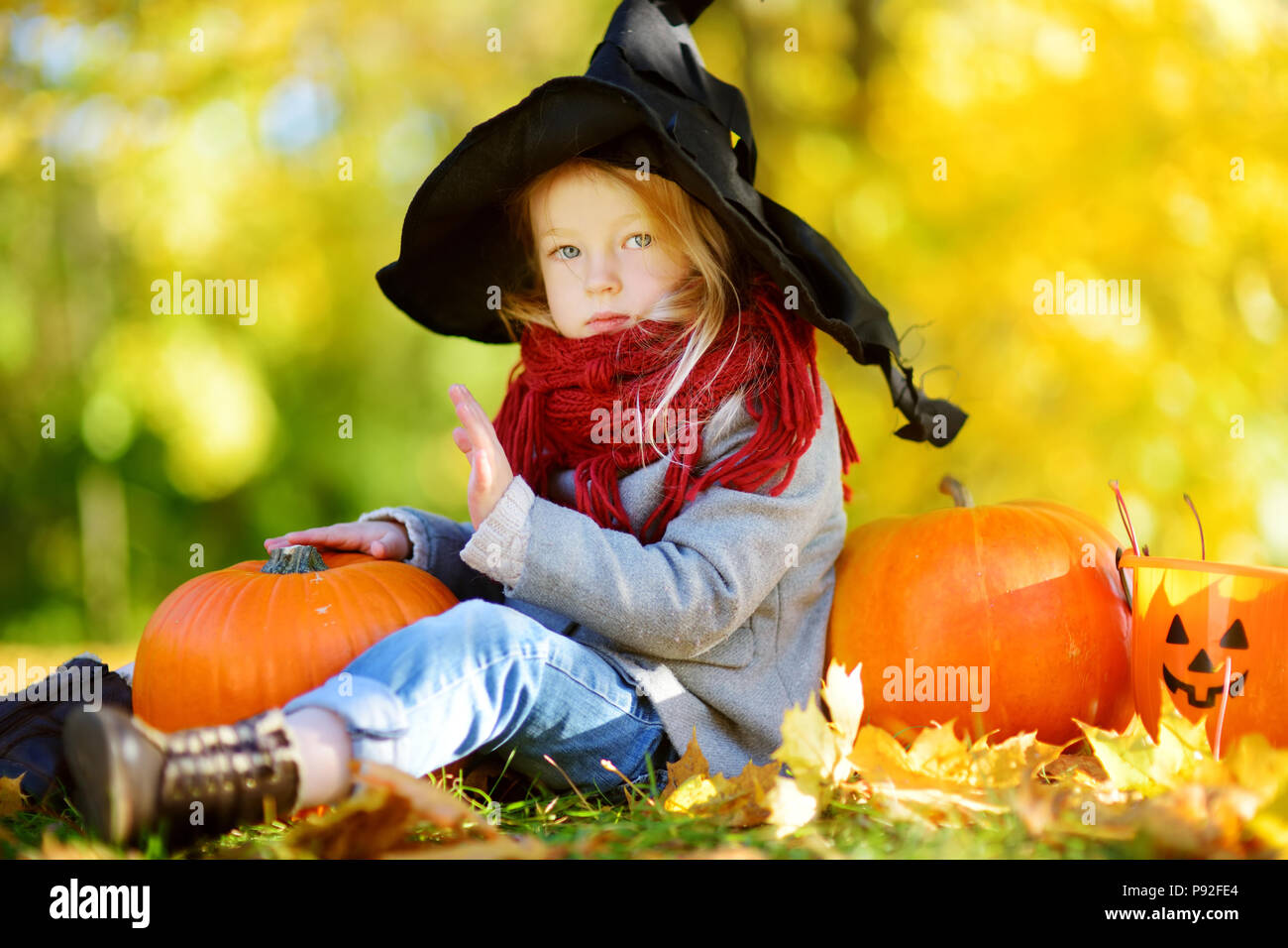 adorable little girl wearing halloween costume having fun on a pumpkin patch on beautiful autumn day happy child playing in autumn park autumn activ
