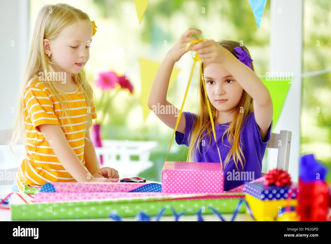 Two Cute Sisters Wrapping Gifts In Colorful Paper Adorable Siblings Birthday Presents Family Fun