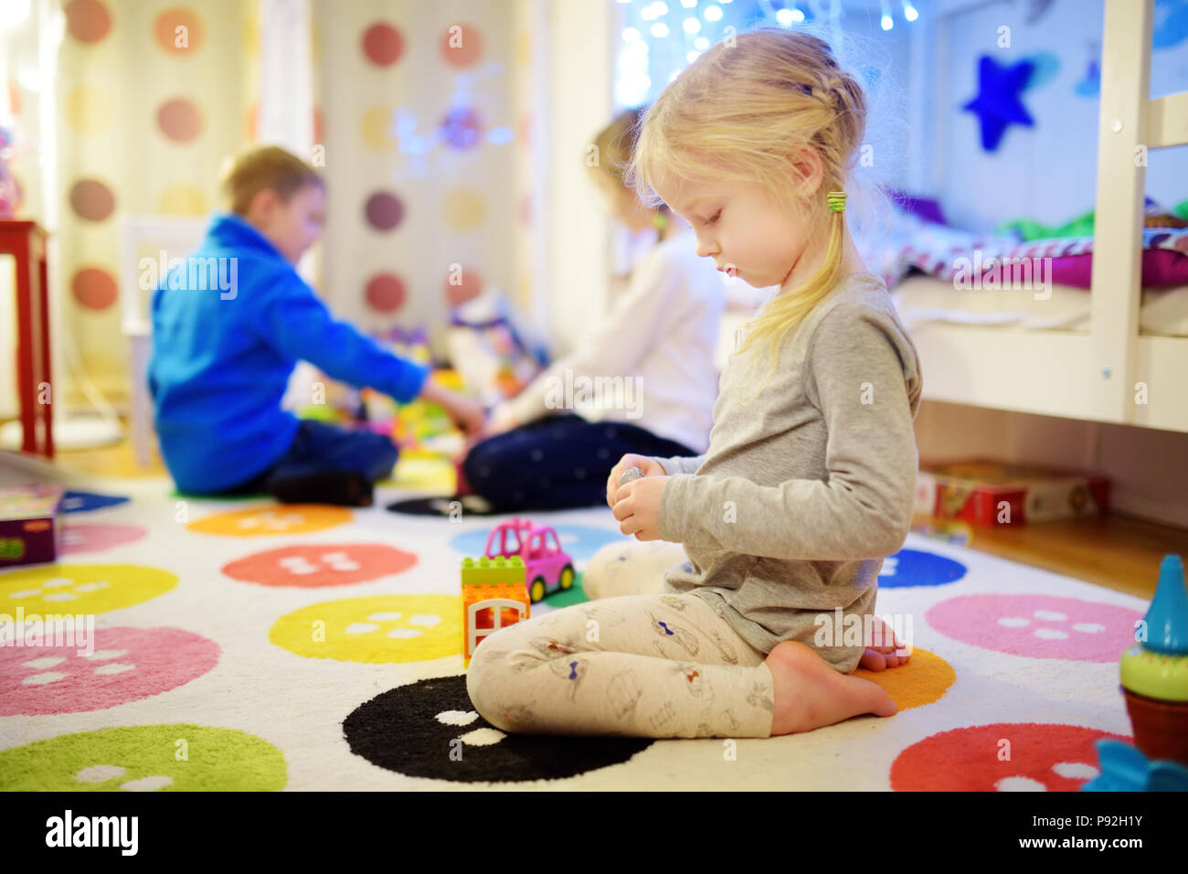 Three Children Playing With Colorful Plastic Blocks At Kids Room