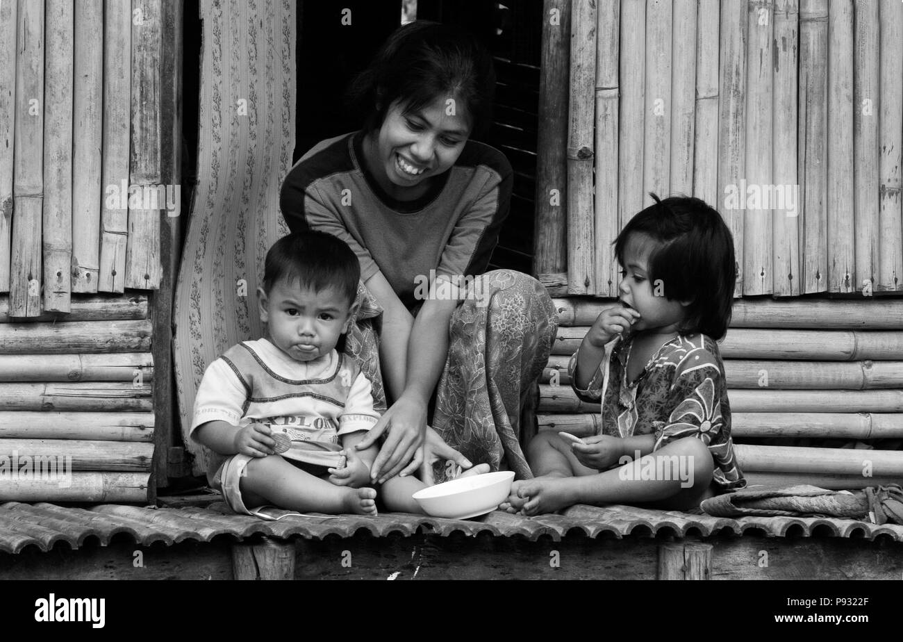 A Thai mother and child on their front porch in the Muslim village of Tung Nang Dam located on the North Andaman Sea - THAILAND - Stock Image