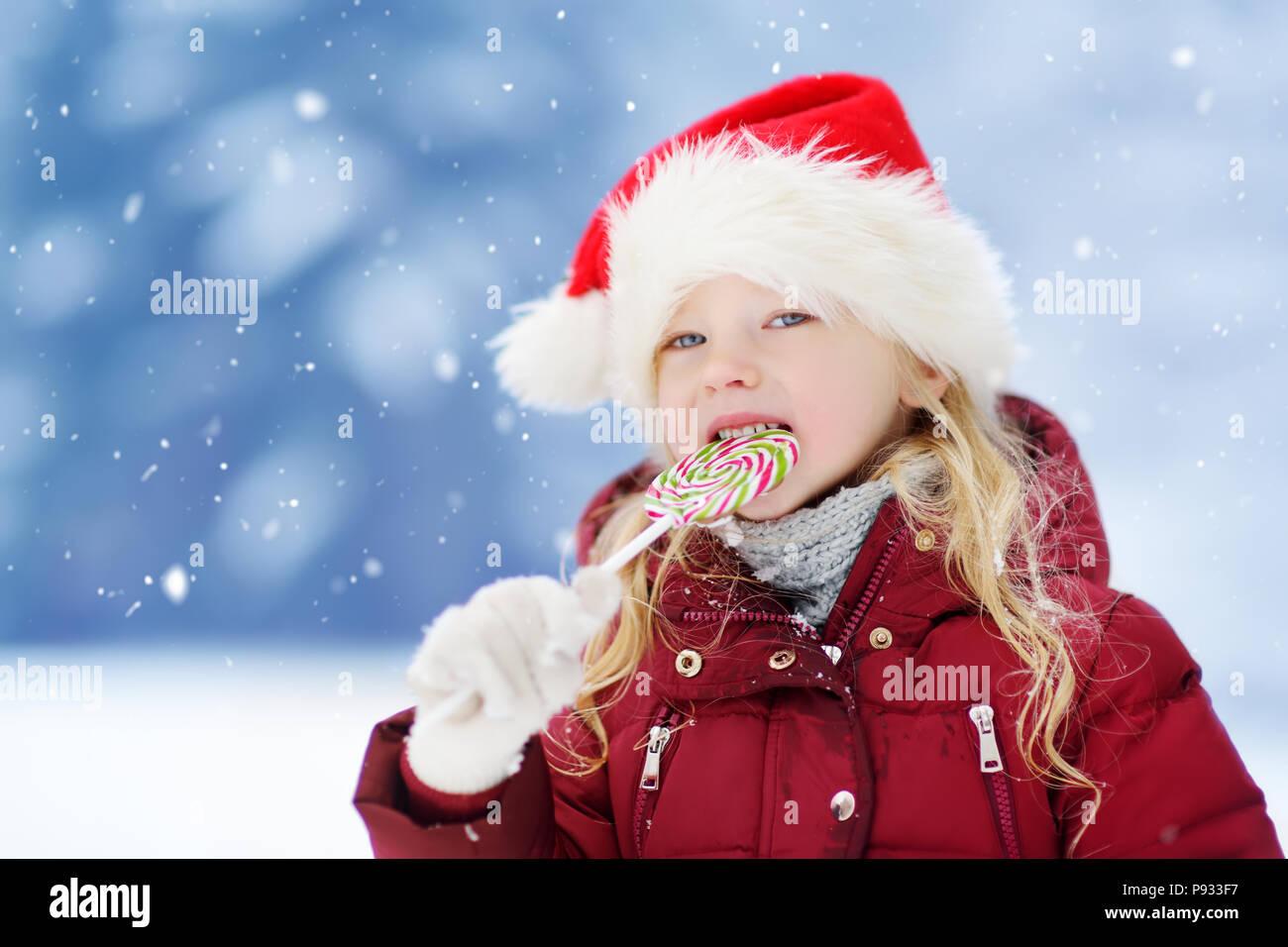 f07e7482e Adorable little girl wearing Santa hat having huge striped Christmas ...