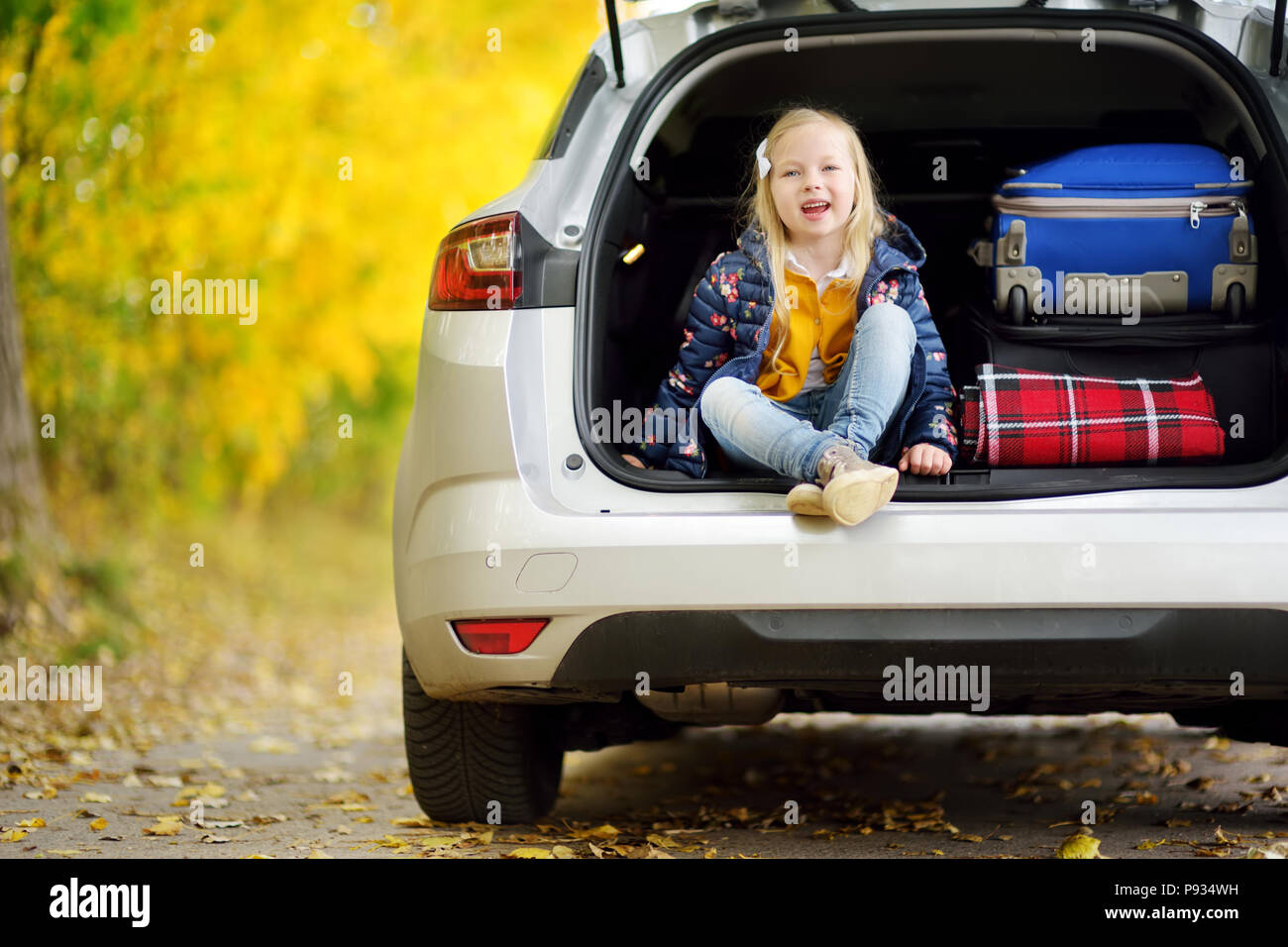 Adorable girl sitting ain a car trunk ready to go on vacations with her parents. Child looking forward for a road trip or travel. Autumn break at scho - Stock Image