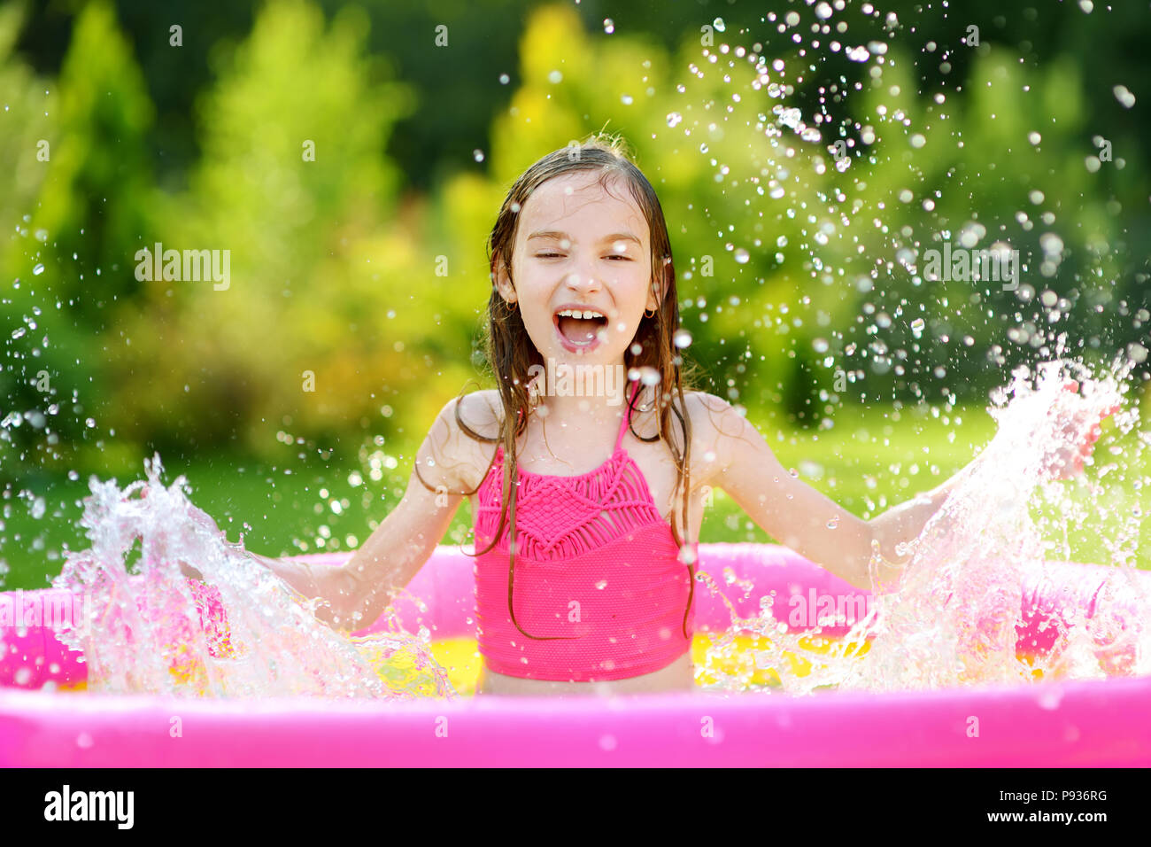 Adorable little girl playing in inflatable baby pool. Happy kid