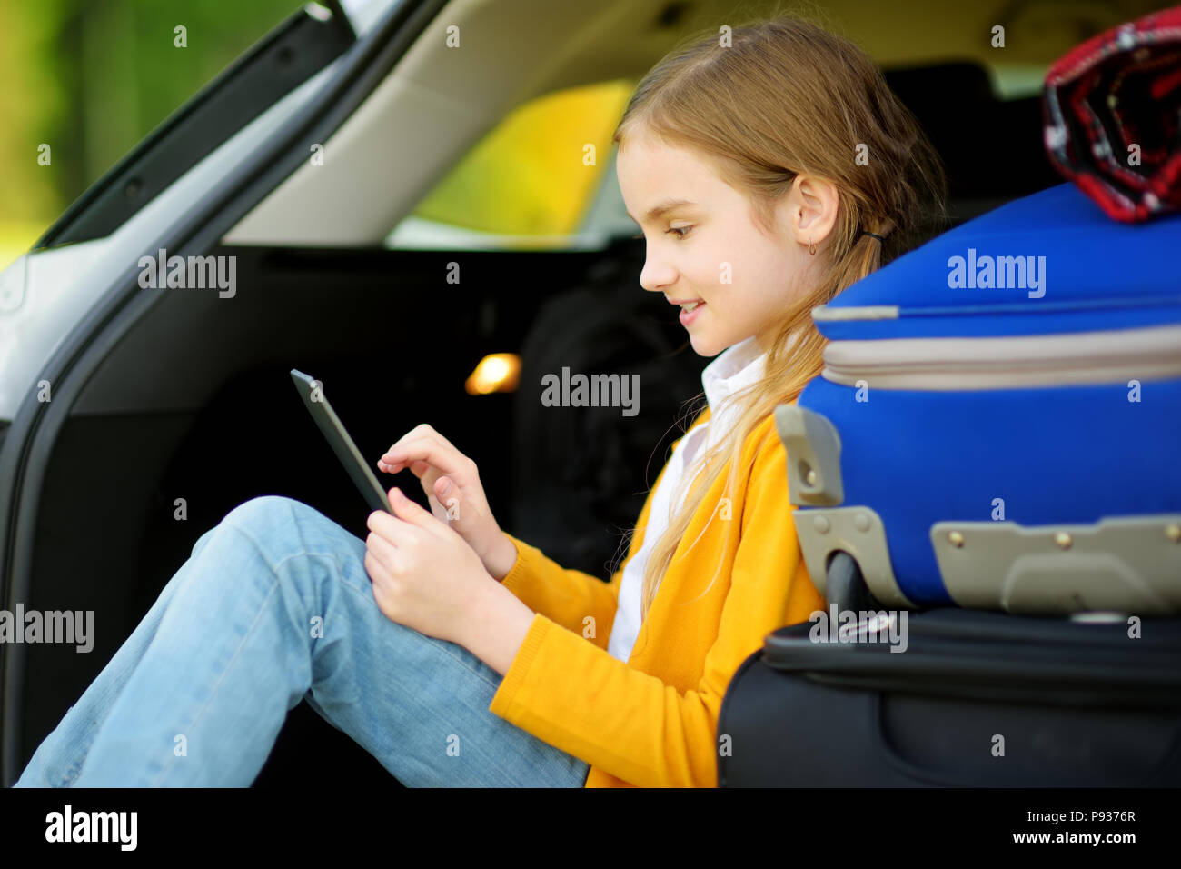 Adorable little girl ready to go on vacations with her parents. Kid sitting in a car trunk and reading her ebook. Traveling by car with kids. - Stock Image
