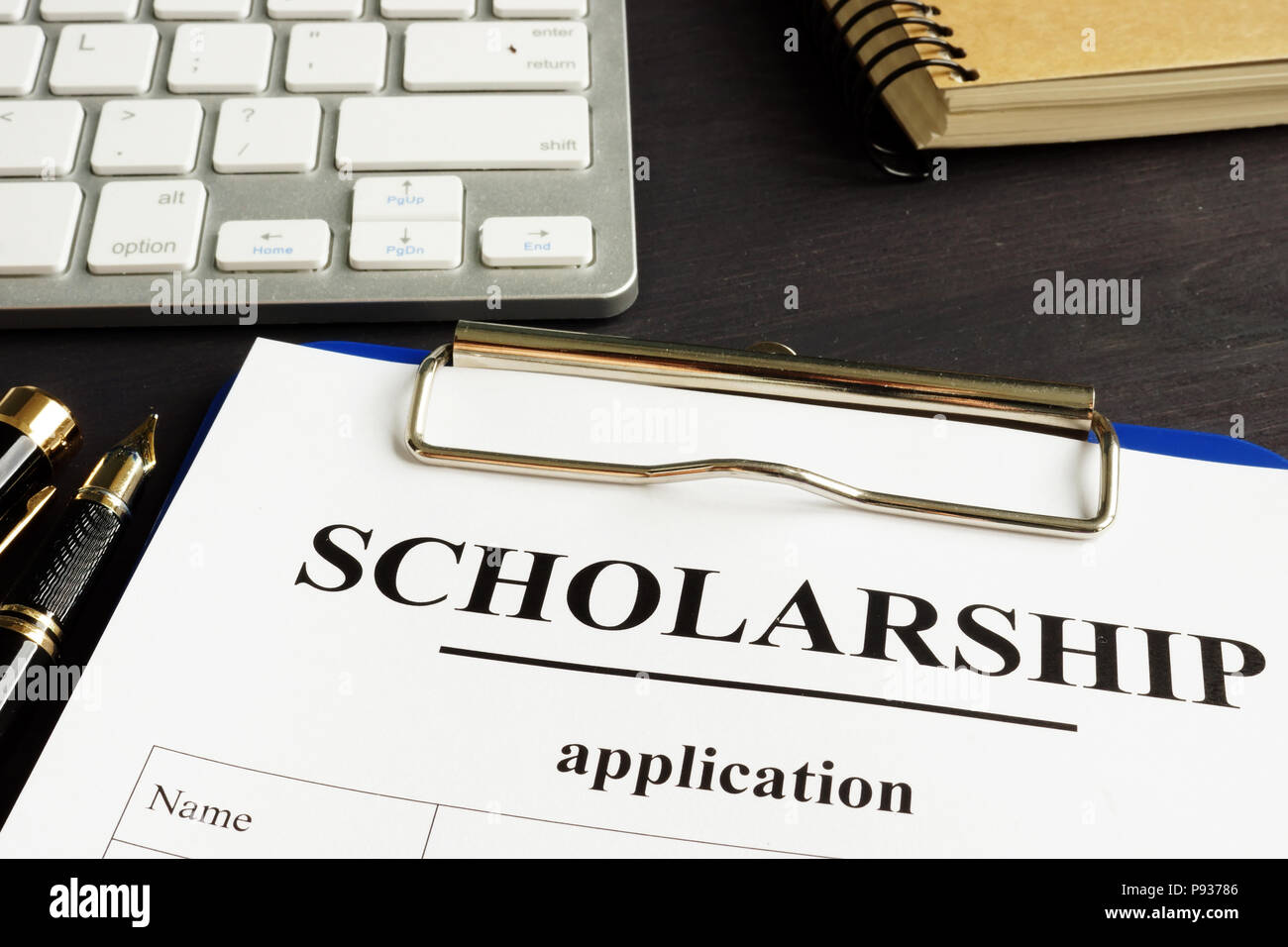 Scholarship application and money for education on a table. - Stock Image