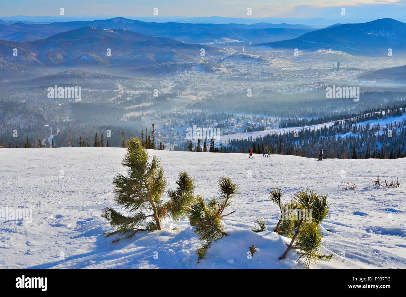 RUSSIA, SIBERIA, SHEREGESH - JANUARY 11, 2016: Sunny morning and ftosty mist over the ski resort Sheregesh - view from top of mountain with littlel pi - Stock Image