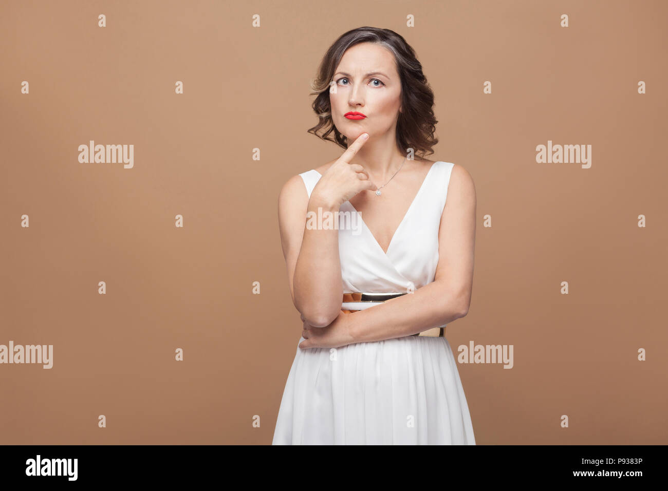 Beautiful middle aged woman thinking and puzzled. Emotional expressing woman in white dress, red lips makeup and dark curly hairstyle. Studio shot, in - Stock Image