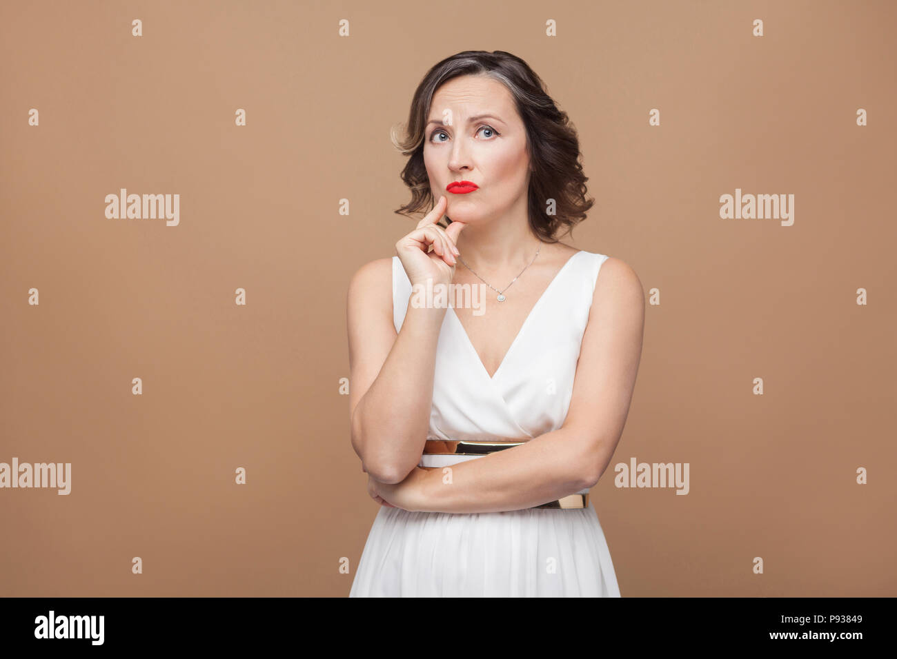 Handsome middle aged woman thinking and puzzled. Emotional expressing woman in white dress, red lips and dark curly hairstyle. Studio shot, indoor, is - Stock Image