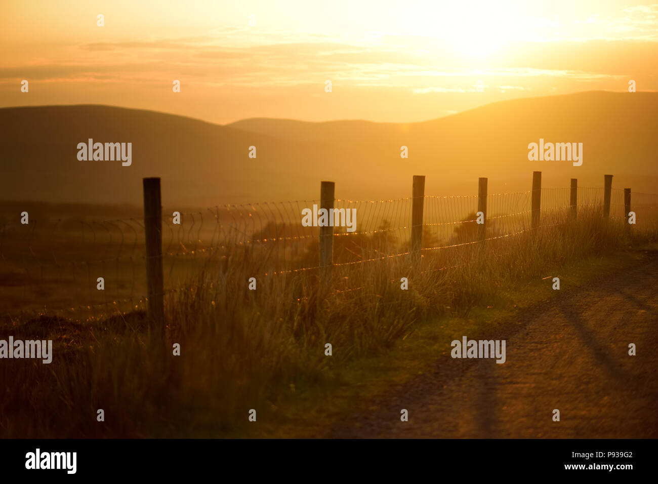 Beautiful sunset in Connemara. Scenic Irish countryside road leading towards magnificent mountains, County Galway, Ireland. - Stock Image