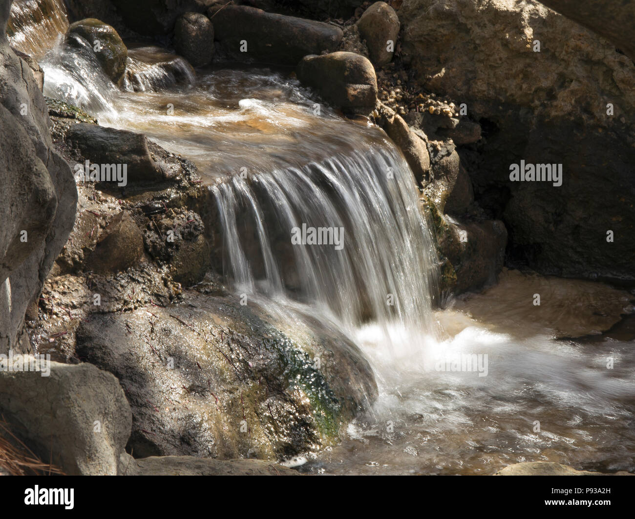 Water swiftly flows over a small waterfall inside the Birmingham Botanical Gardent - Stock Image