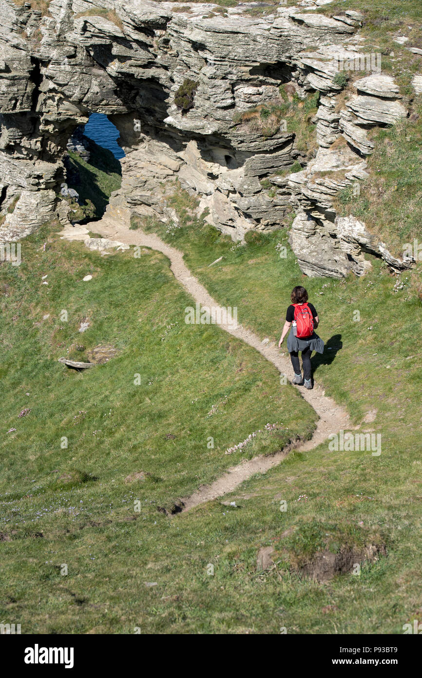 Female hiker walking on the South West Coast Path towards the Ladies Window rock arch near Boscastle in Cornwall, England, UK - Stock Image