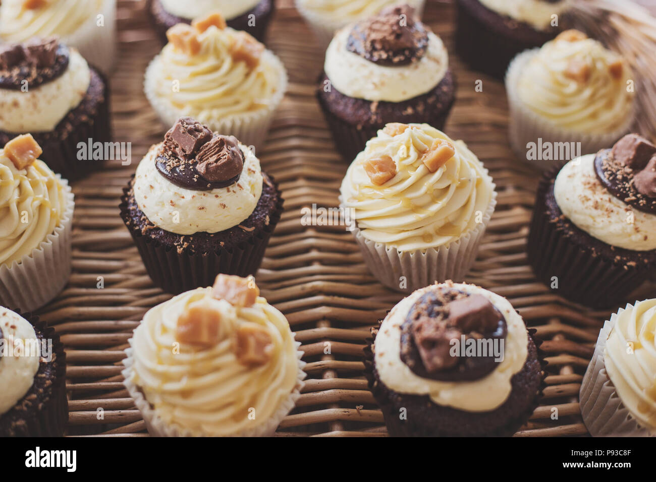caramel and chocolate cupcakes laid out in a presentation box - Stock Image
