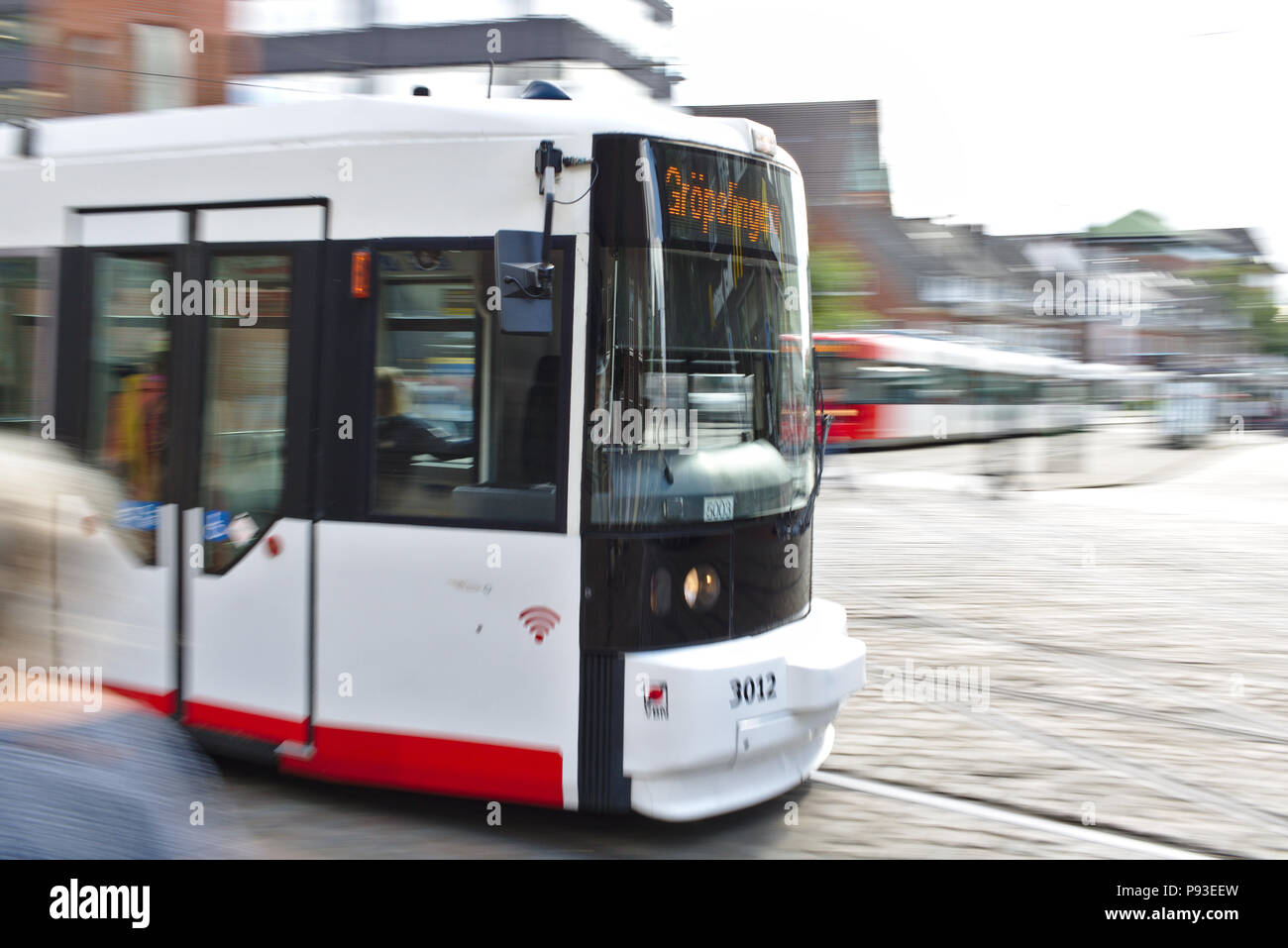 Bremen, Germany - July 10th, 2018 - First car of a tram passing by (motion blur, long exposure) - Stock Image