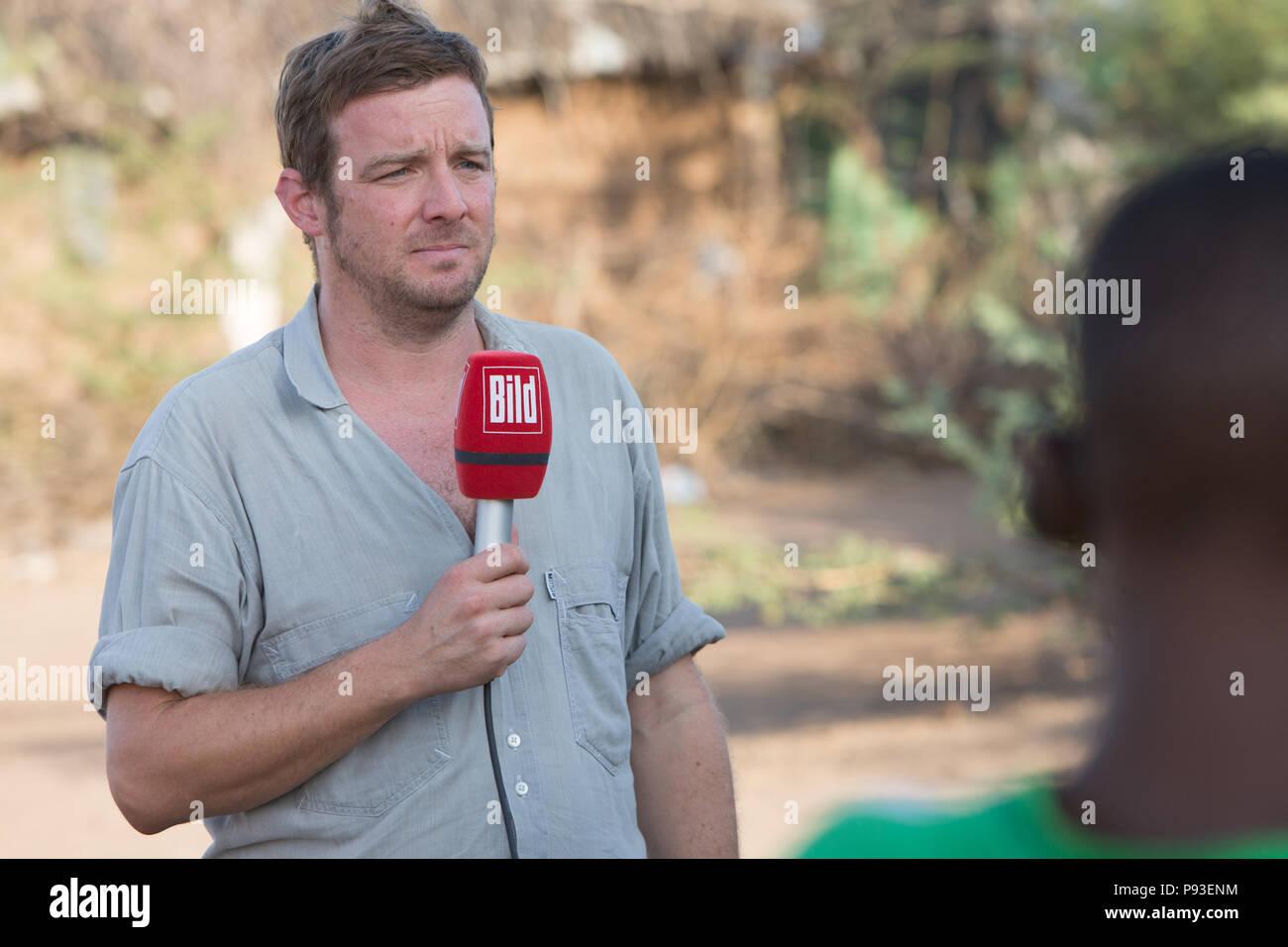 Kakuma, Kenya - Kai Feldhaus, reporter and journalist of the Bild newspaper speaks in the refugee camp Kakuma an announcement text into the microphone. - Stock Image