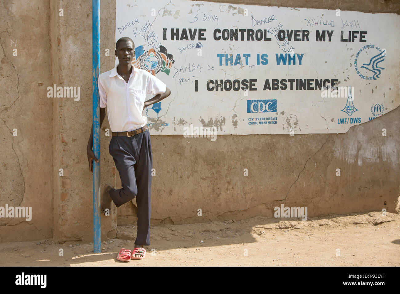 Kakuma, Kenya - Student Leaning Against Kakuma Refugee Camp On Wall With Inscription - I HAVE CONTROL OVER MY LIFE. THAT IS WHY I CHOOSE ABSTINENTE. - Stock Image