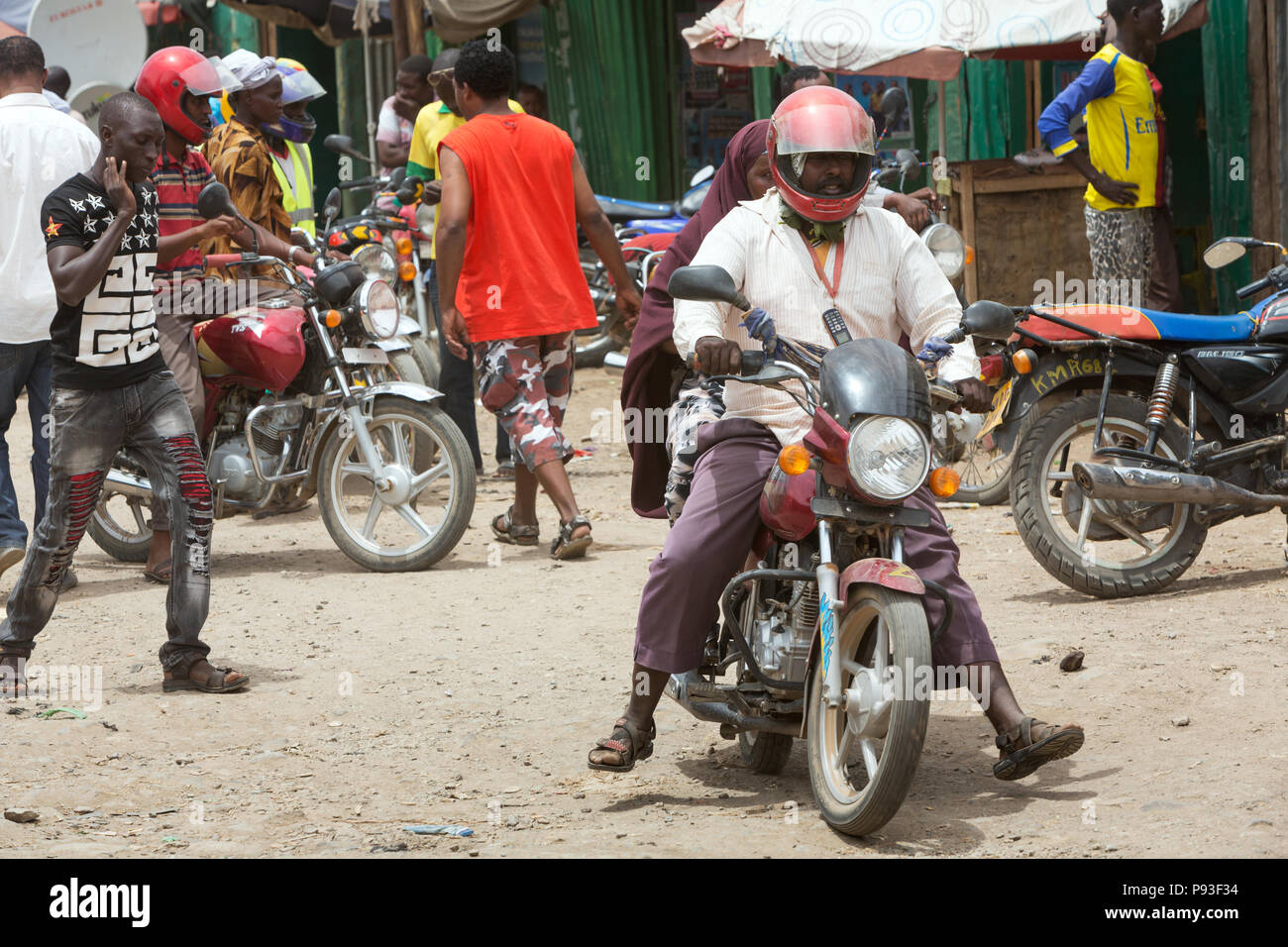 Kakuma, Kenya - Street scene with people and motorcycles. Motorcycle traffic on a busy unpaved road. - Stock Image