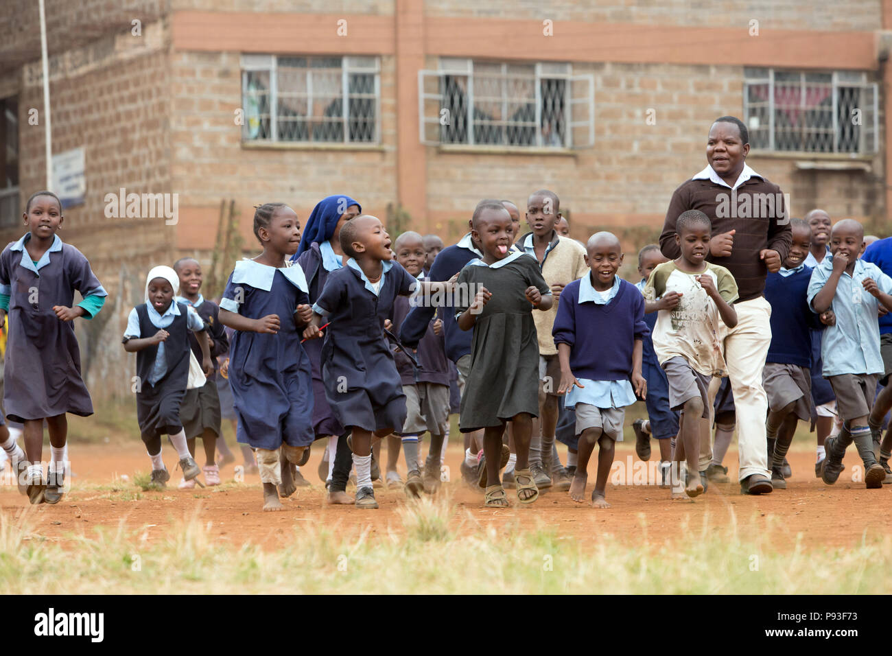 Nairobi, Kenya - Students in school uniforms walk with a teacher in the schoolyard of St. John's Community Center Pumwani. Stock Photo