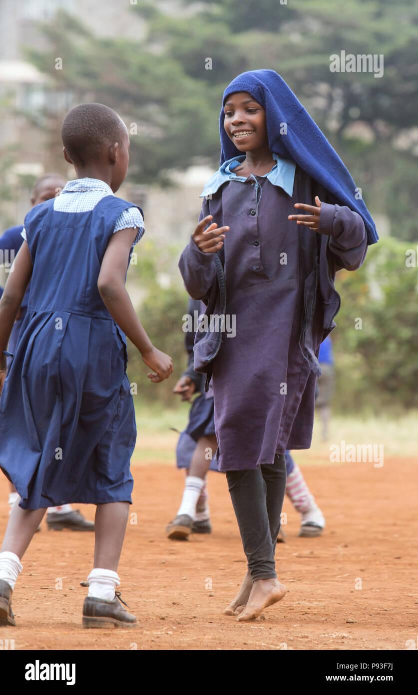 Nairobi, Kenya - School uniforms play in the schoolyard of St. John's Community Center Pumwani. - Stock Image