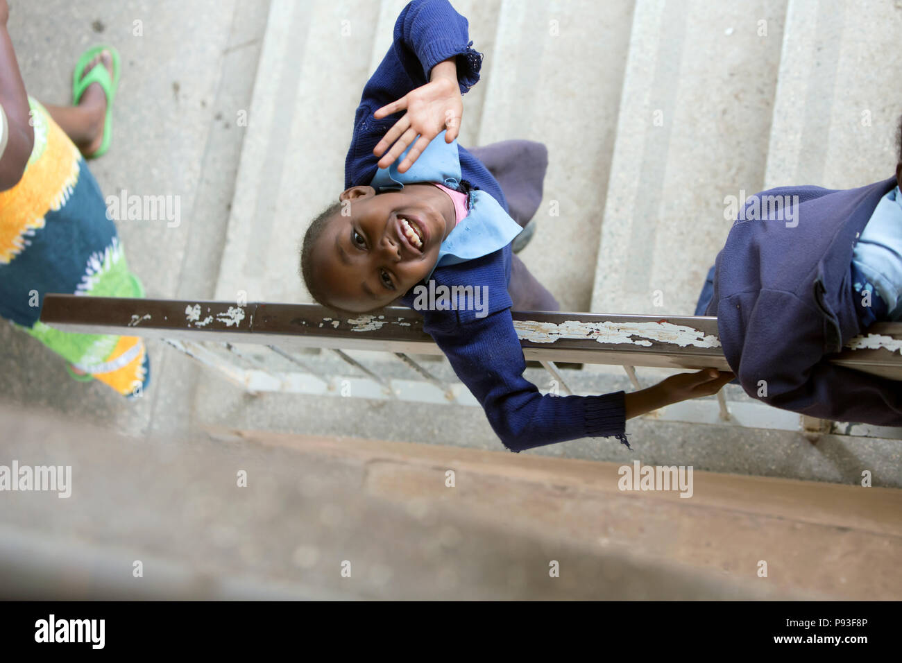 Nairobi, Kenya - School uniform student stands in the stairwell of St. John's Community Center Pumwani looking at the viewer. - Stock Image
