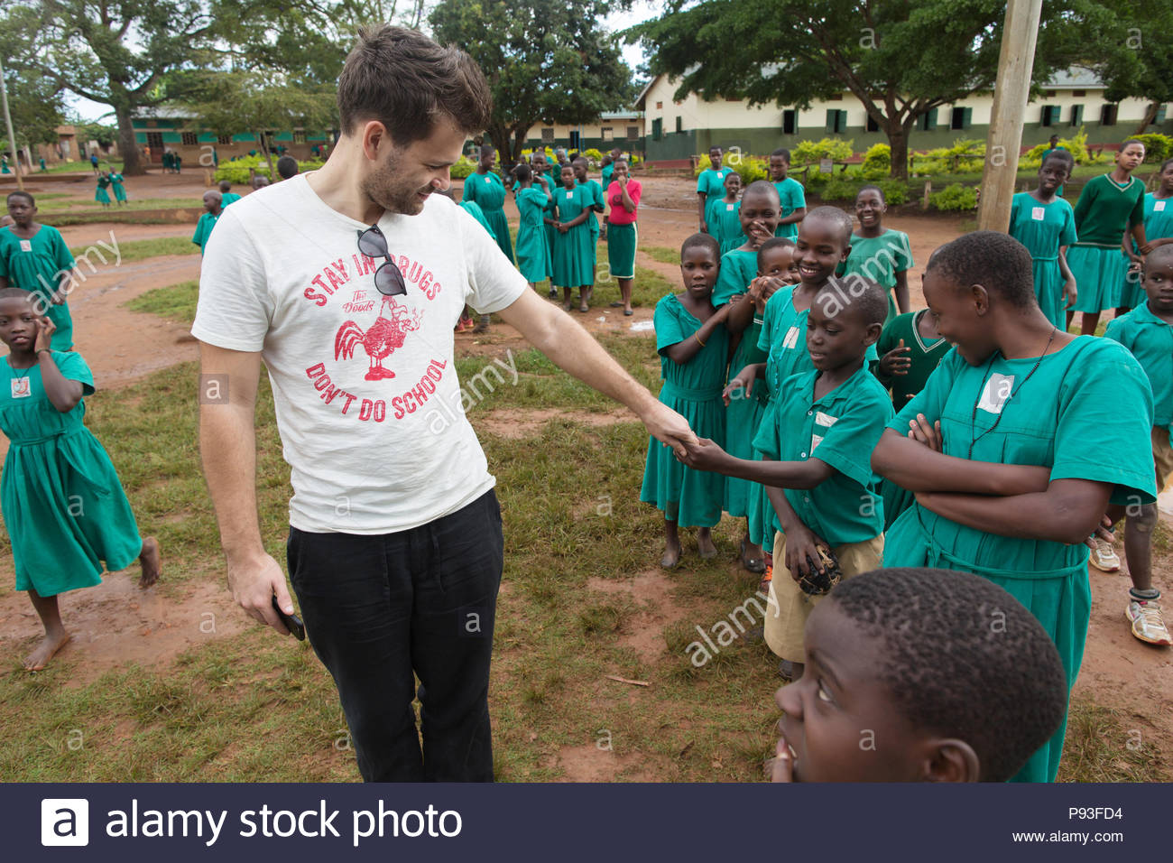 Bombo, Uganda - YouTuber Thilo Jung of Jung and Naiv is being watched by elementary school students at the St. Joseph's Bombo mixed primary school playground. - Stock Image