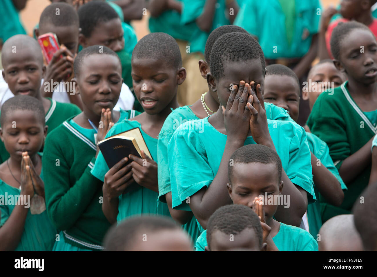 Bombo, Uganda - Praying students at the school appeal in the schoolyard of St. Joseph's Bombo mixed primary school. - Stock Image