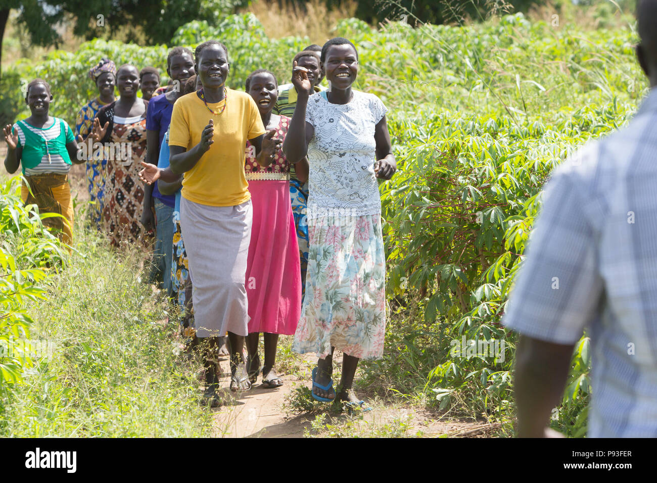 Adjumani, Uganda - Women of a village community meet a singing and dancing on a path. - Stock Image