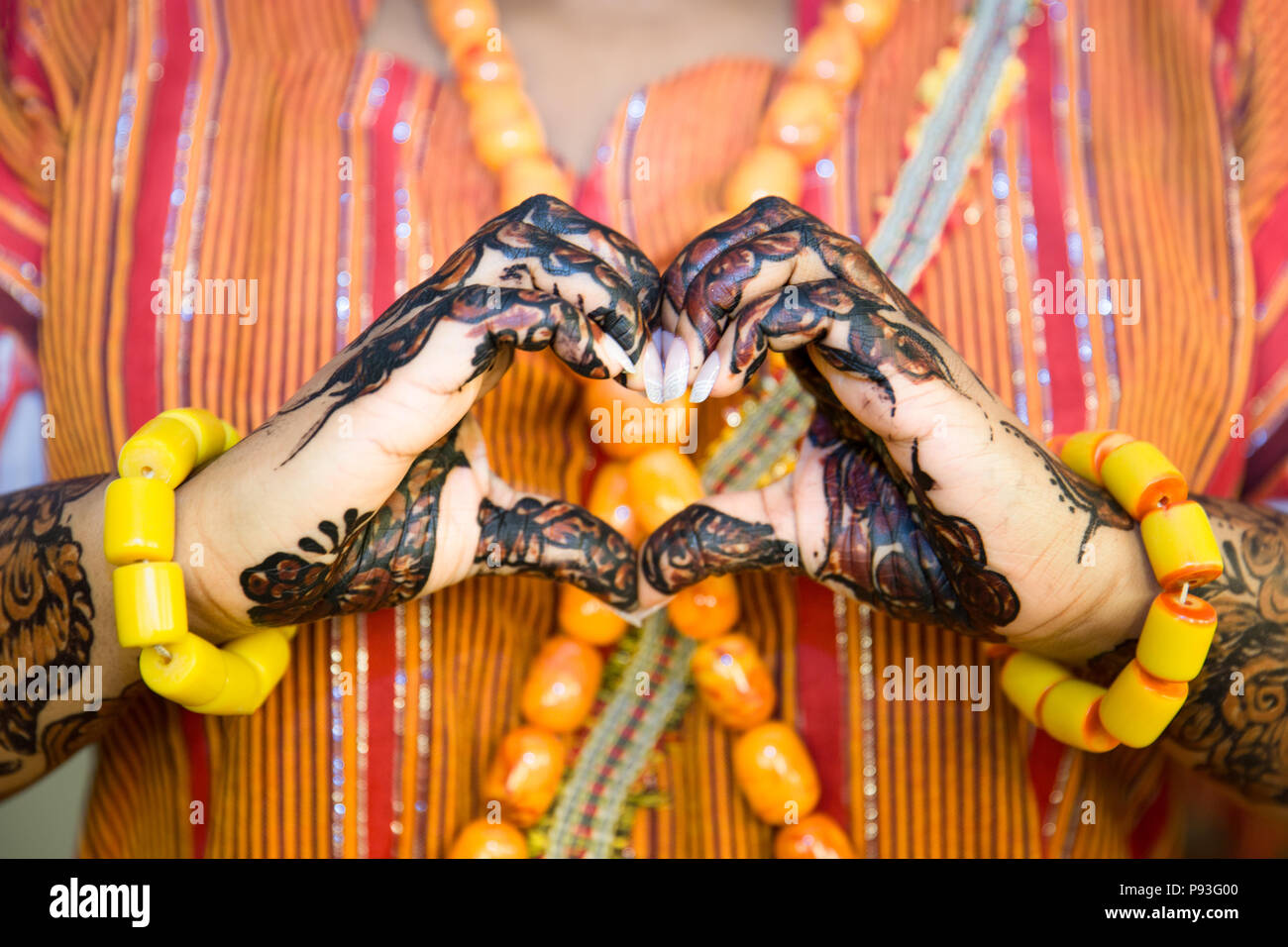 African Woman making a Heart Shape with Henna Painted Hands Stock Photo