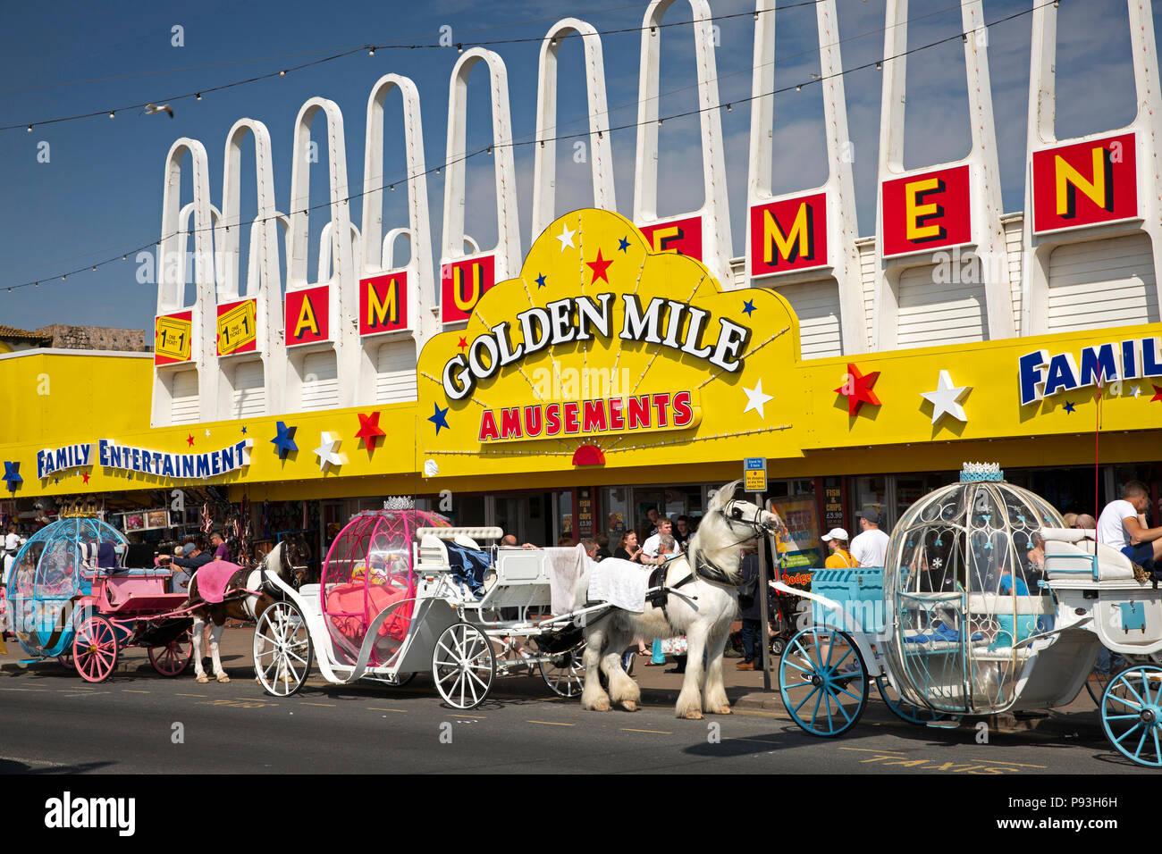 UK, England, Lancashire, Blackpool, Promenade, passenger carriages outside Golden Mile amusement arcade - Stock Image