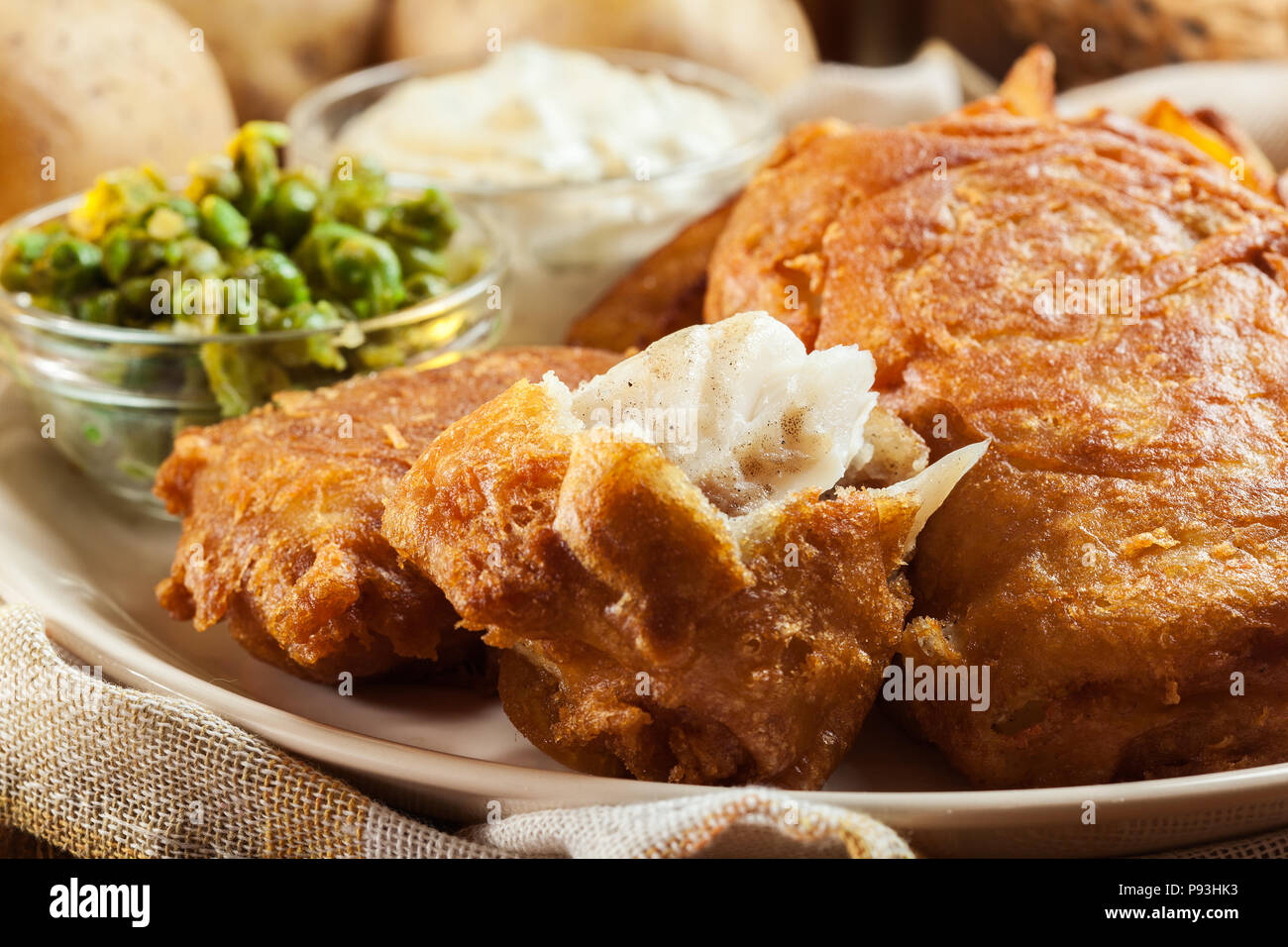 Traditional fish in beer batter and chips with green pea and tartar sauce Stock Photo
