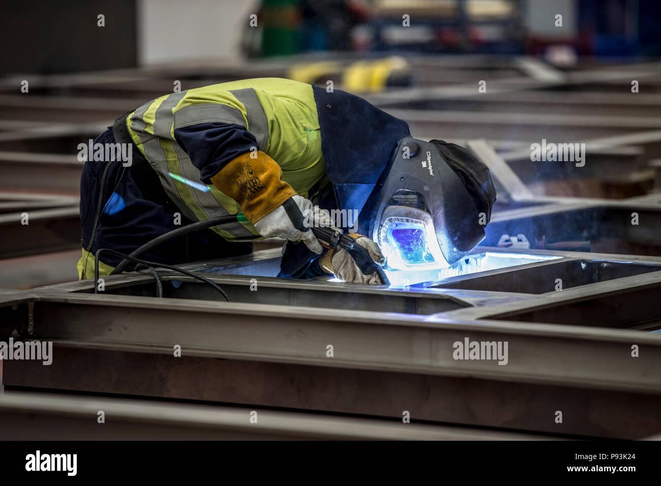 Welder wearing protective equipment welding - Stock Image