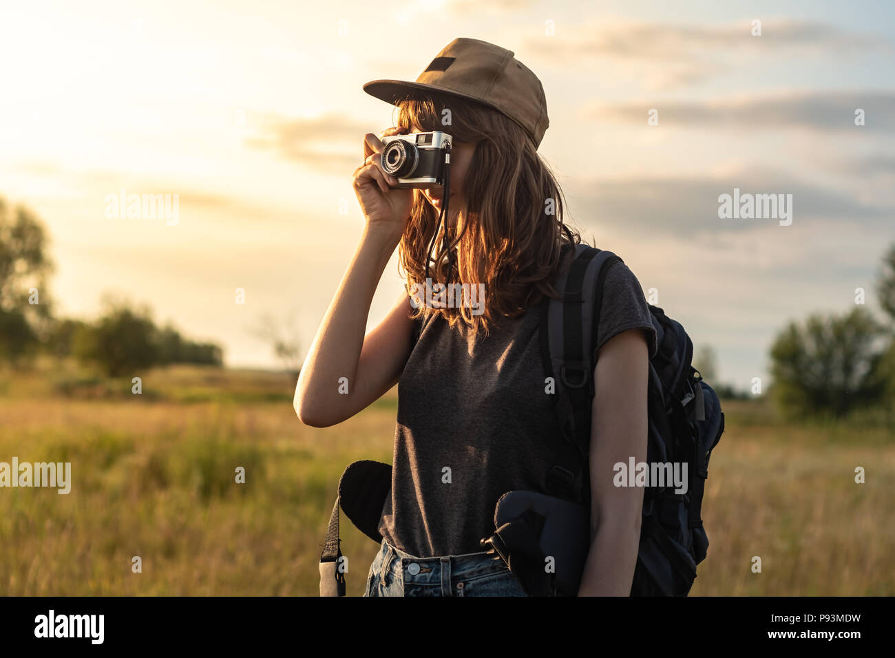 Young female tourist taking photo at hiking trip. Woman with backpack stands at sunset and photographs beautiful rural area - Stock Image
