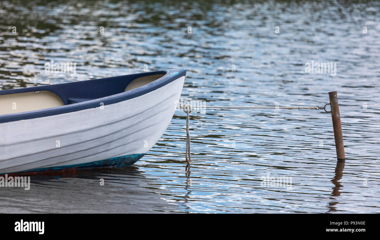 Abstract conceptual selective focus view of bow of moored rowing boat tied up and anchored on a tranquil lake - Stock Image
