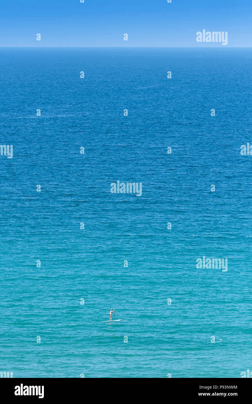 A woman on a paddle board in the sea. - Stock Image