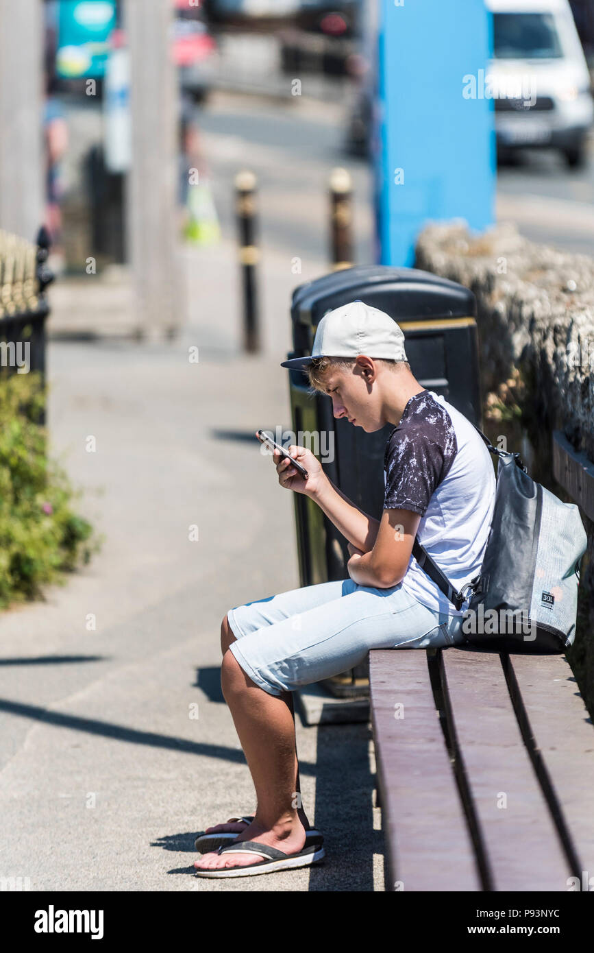 A young teenage boy engrossed in his smartphone. - Stock Image