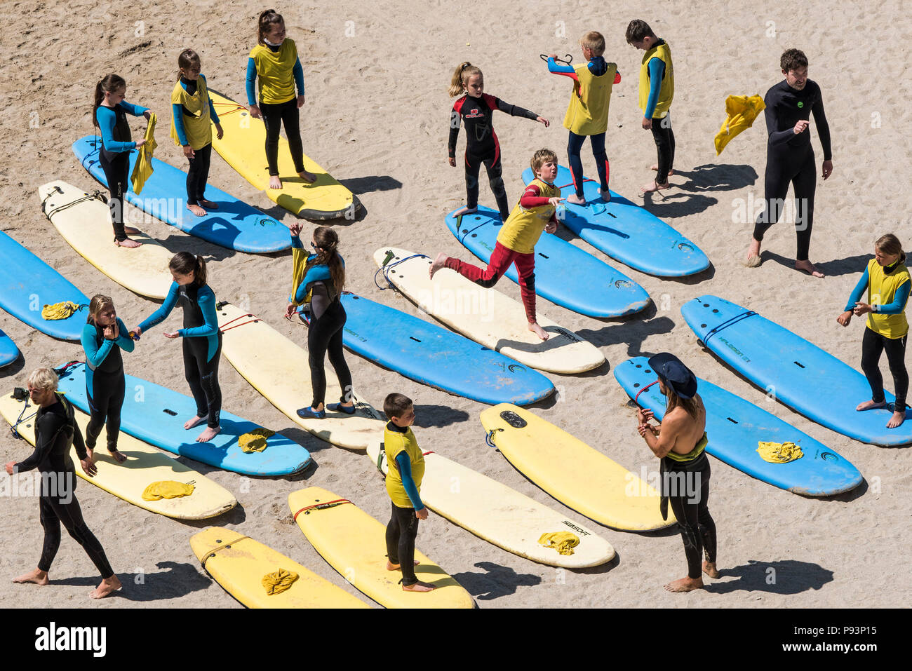 A group of children preparing for a surf lesson on Tolcarne Beach in Newquay in Cornwall. - Stock Image
