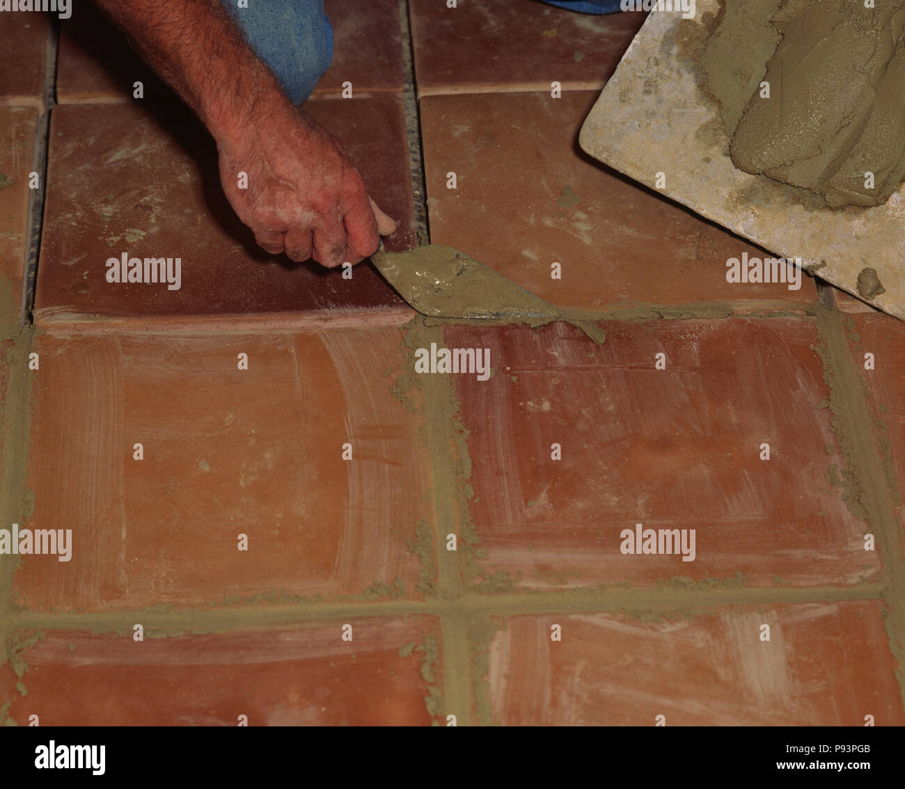 Close-up of hand with trowel laying terracotta floor tiles FOR ...
