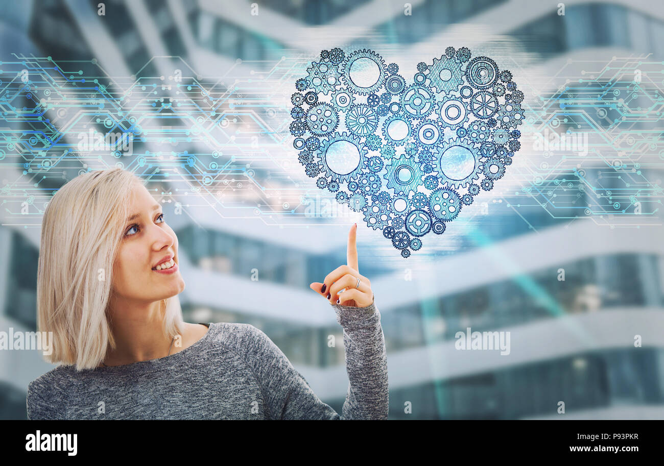 Portrait of smiling woman pointing finger up showing a gear heart hologram. Future technology artificial intelligence health protection. Human charact - Stock Image