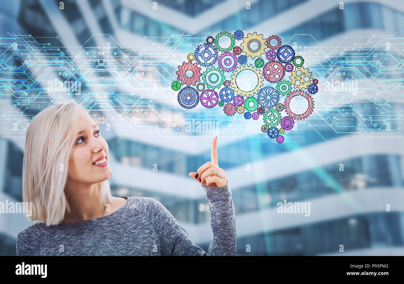 Portrait of smiling woman pointing finger up showing a gear brain hologram. Future technology artificial intelligence. Human logic and emotions concep - Stock Image