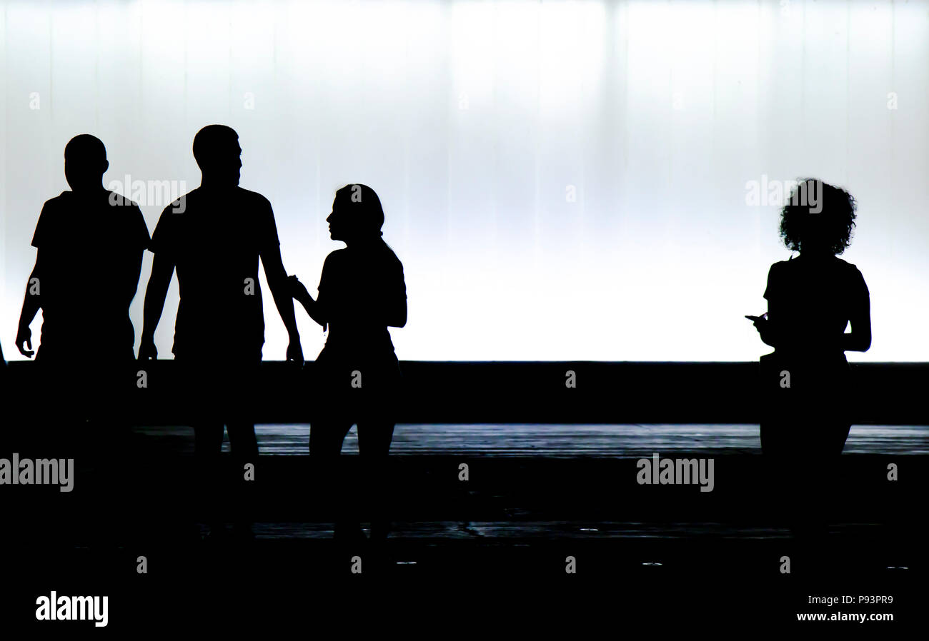Blurry silhouettes of three young friends students and a boy is looking at a new girl with curly hair standing alone in the black and white night Stock Photo