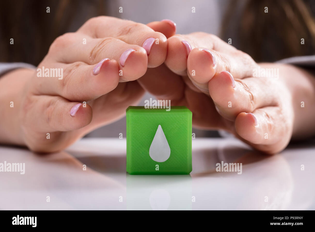 Woman's Hand Protecting Green Cubic Block With Water Drop Icon Over Desk - Stock Image