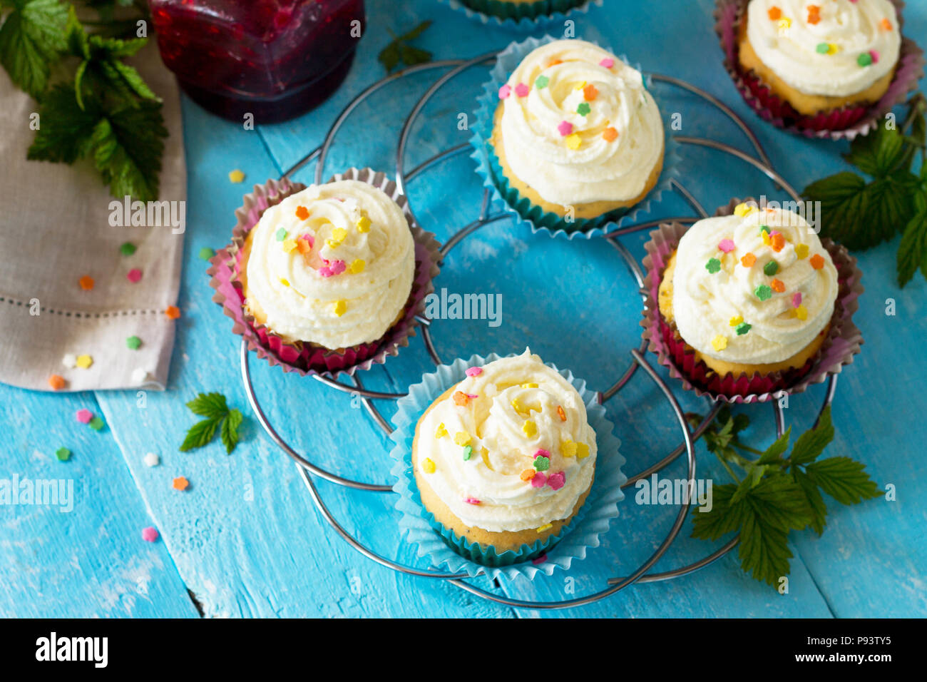 Birthday cupcake with buttercream icing and raspberry jam a wooden table. Copy space. - Stock Image