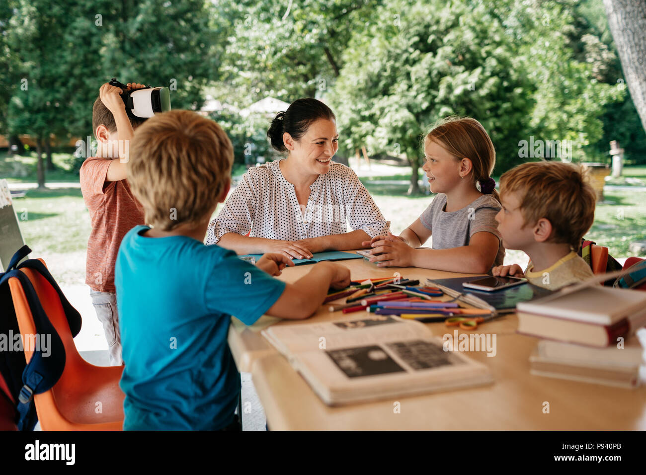 Young students engaged in a class outside in the fresh air. Outdoor learning - school children enjoying a lesson with their teacher. - Stock Image