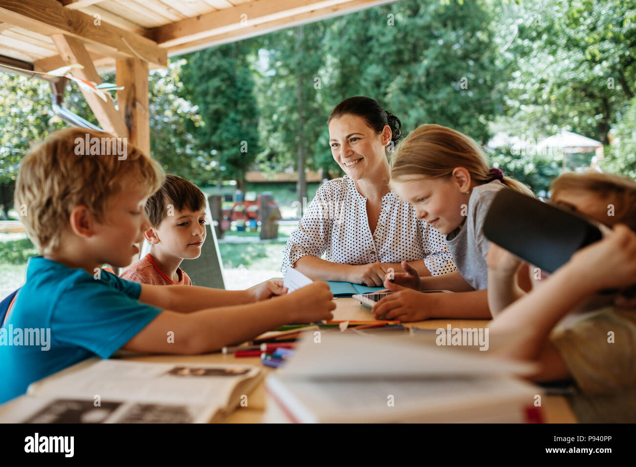Group of young schoolchildren having a lesson. Children learning together with a teacher outside. - Stock Image