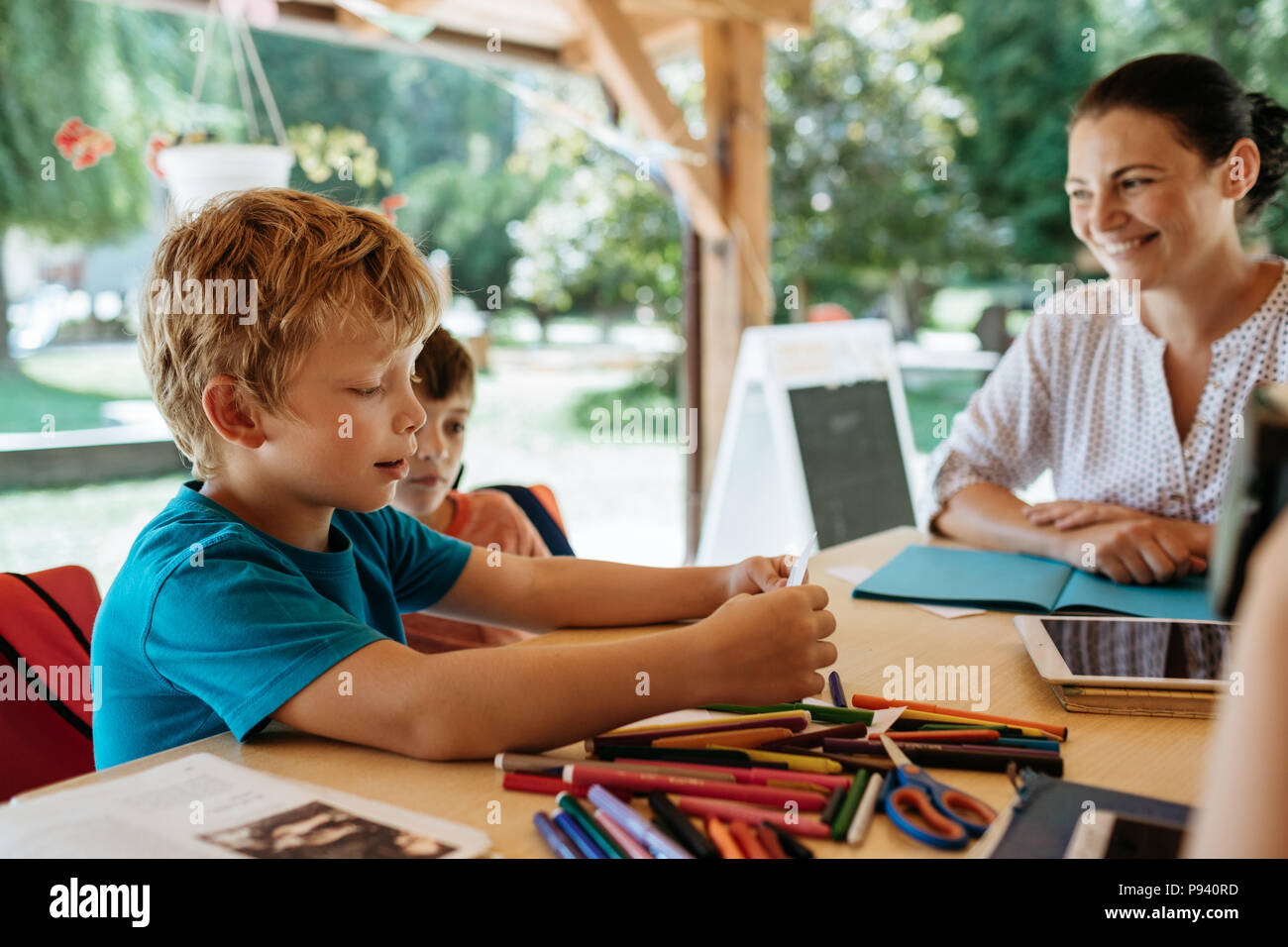 Cheerful teacher encouraging children to read. Schoolboy reading aloud to his peers and teacher. - Stock Image