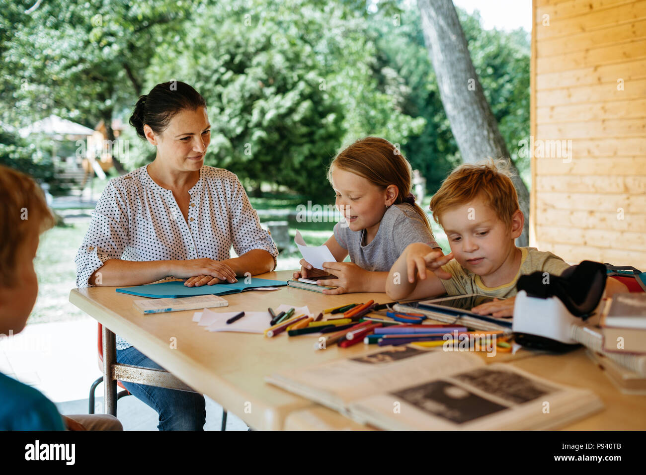 Young school girl reading aloud to her mother and class mates. Homeschooling - children learning with a teacher outside in a park. - Stock Image