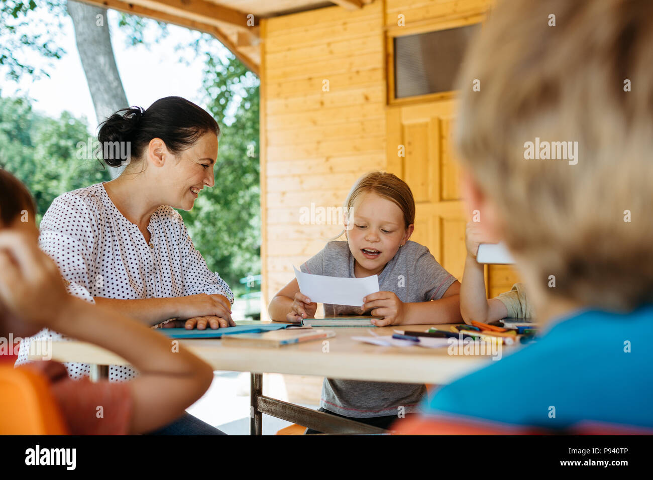 Happy teacher listening to a young girl reading. Teacher encouraging a student to read. - Stock Image