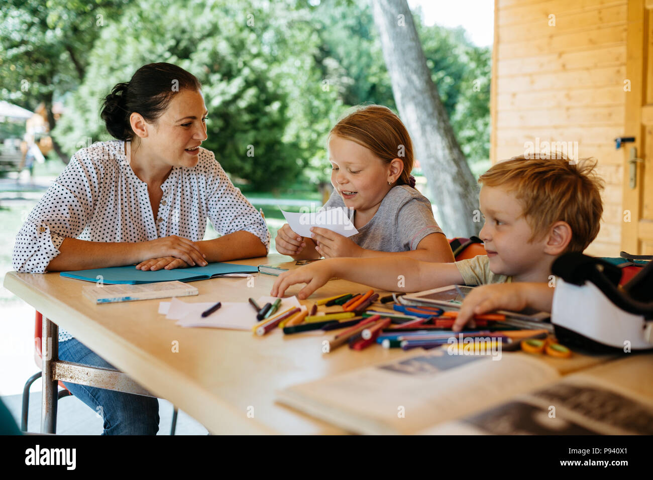 Outdoor learning - educational concept. Young students learning together with their mother outside in a park. - Stock Image