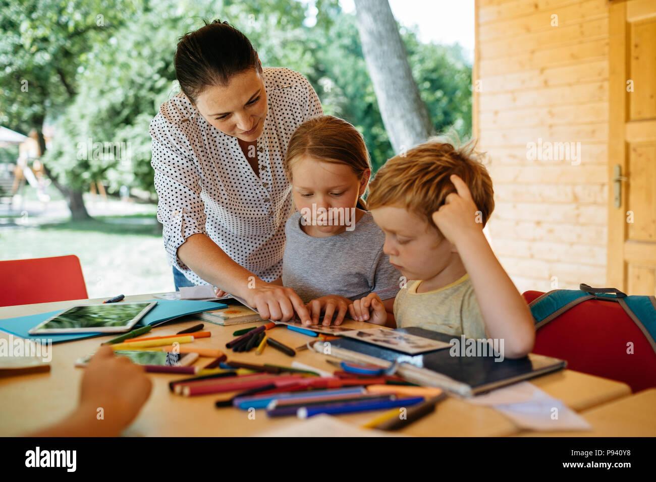 Teacher - student interaction. Teacher explaining to pupils. - Stock Image