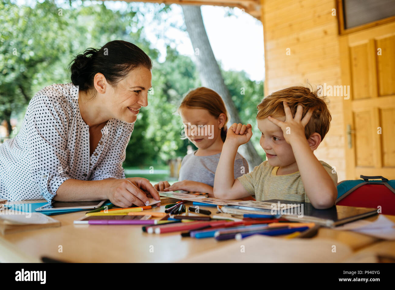 Teacher and students reading books together. Friendly teacher listening to a young boy reading and explaining. - Stock Image