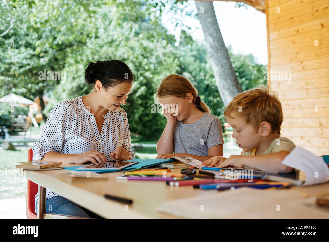 Children having fun reading a book with their mother outside in a park. Mother homeschooling her children and reading with them. - Stock Image